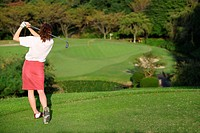 Rear view of a woman teeing off on a short hole