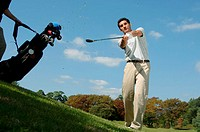 Low angle view of a man playing a golf shot