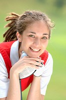 Woman smiling at the camera holding a golf club