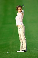 Woman posing in front of the camera holding a golf club