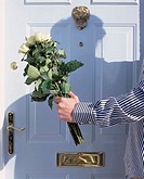 Man with flowers by front door