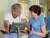 Man on exercise bike with his wife (thumbnail)