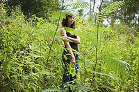 Young woman standing amongst fern
