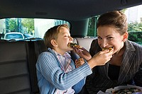 Mother and son eating in car