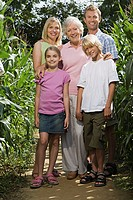 Family standing between corn plants