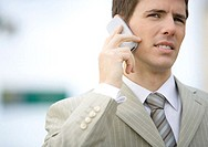 Businessman using cell phone, squinting