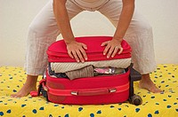 Woman trying to squeeze her packed travel case shut