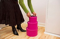Stack of three pink gift boxes on a wooden floor.