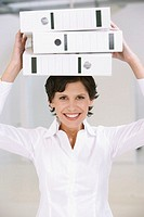 Businesswoman carrying three document file boxes