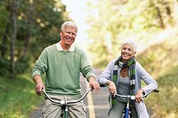 Senior couple cycling along a country road