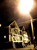 Old Victorian houses in Upstate New York captured at night, highlighted by the ghostly glow of a streetlight. USA