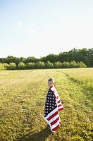 Boy draped in an American flag standing in a field (thumbnail)