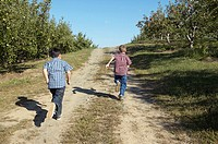 Two boys running down a dirt road