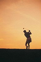 Silhouette of man playing golf.