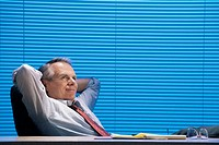 Businessman relaxing in office.