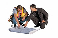 Construction worker and businessman looking at blueprints.