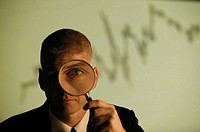 Man holding magnifying glass with graph behind him.