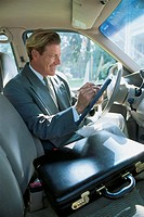 Businessman with tablet PC in car
