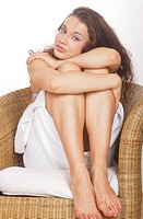 Young Woman in Towel Hugging her Knees