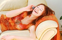 Portrait of Young Woman Lying Down Laughing and Talking on Mobile Phone