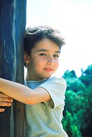 Young boy smiling hugging a wooden post