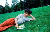Young boy lying on the grass holding a book