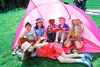 Young children sitting in a tent with candy