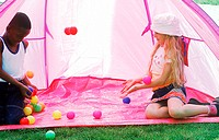 Two young children playing with colored balls in a tent