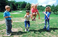 Young children playing with a skipping rope