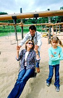 Husband pushing wife on a swing while daughter stands nearby