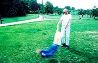Grandfather swinging girl in air