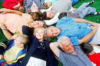 High angle view of a family lying down in a circle on the grass