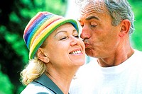 Close-up of an elderly man kissing a woman on the cheek