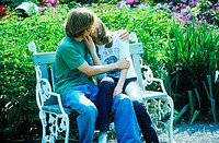 Young couple sitting on a park bench kissing