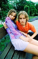 Portrait of young couple sitting on a park bench (thumbnail)
