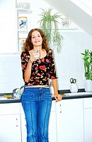 Portrait of a young woman holding a glass of milk in the kitchen (thumbnail)