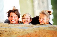 Portrait of a Young man and two young women behind a wooden log