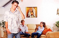 Young man talking on a mobile phone and a young couple sitting on a sofa
