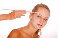 Hand putting a face pack on a woman's face with a brush