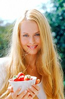 Portrait of young woman holding a bowl of strawberries