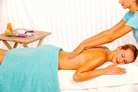 Young woman getting a back massaged by a female masseuse