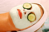 Young woman with a face pack and cucumber slices on her eyes