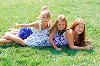 Three young girls lying on each other in a park (thumbnail)