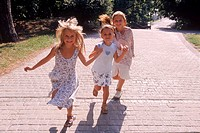 Three girls running in a park