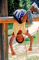A young boy hanging from a jungle gym