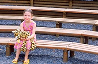 Portrait of a young girl sitting on wooden bench holding a stuffed toy