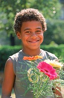 Portrait of a young boy holding flowers