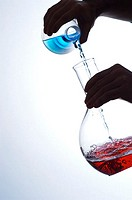 Close-up of a person pouring liquid into a beaker