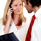 Businesswoman talking on a mobile phone looking at a businessman