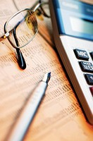 Close-up of a pen with eyeglasses and a calculator on a financial newspaper